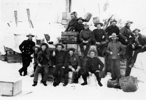 Image from Glenbow's archival photographs of members of the North-West Mounted Police sitting on crates at the summit of Chilkoot Pass.