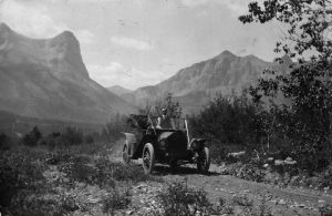 An old-fashioned car travels along a dirt road near Canmore in the Bow Valley in 1910. Two mountains can be seen in the background