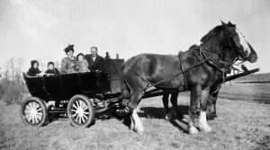 a photograph of a car with its motor removed turned into a wagon and hauled by a pair of horses.