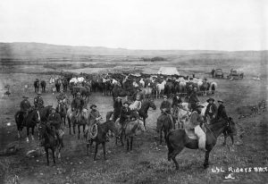 A group of cowboys on horseback in 1899 with a herd of horses in the background.