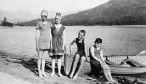 Image from Glenbow's archival photographs of three children and a woman in their bathing with a wooden row boat at Kootenay Lake in 1922.
