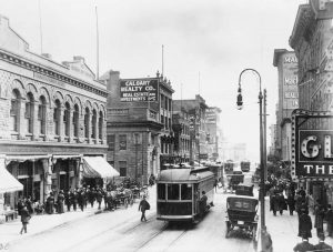 A view of Calgary's Eighth Avenue in 1912 with sandstone brick buildings, street cars and horse-drawn wagons.