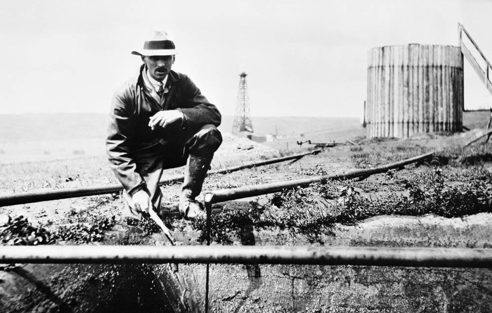 Glenbow Museum founder Eric Harvie kneeling next to pipe of flowing oil.