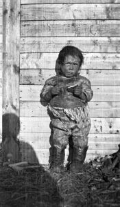 Image from Glenbow's archival photographs of a young Inuit child wearing animal skin clothing standing against the wall of a wooden building in northern Canada.