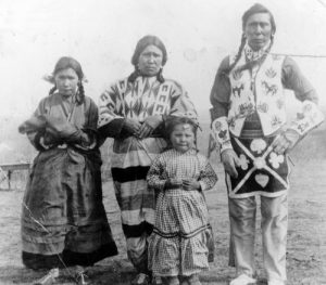 Johnny Good Rider posing for a photograph with his family, from the Blackfoot or Siksika Nation in the 1930s.