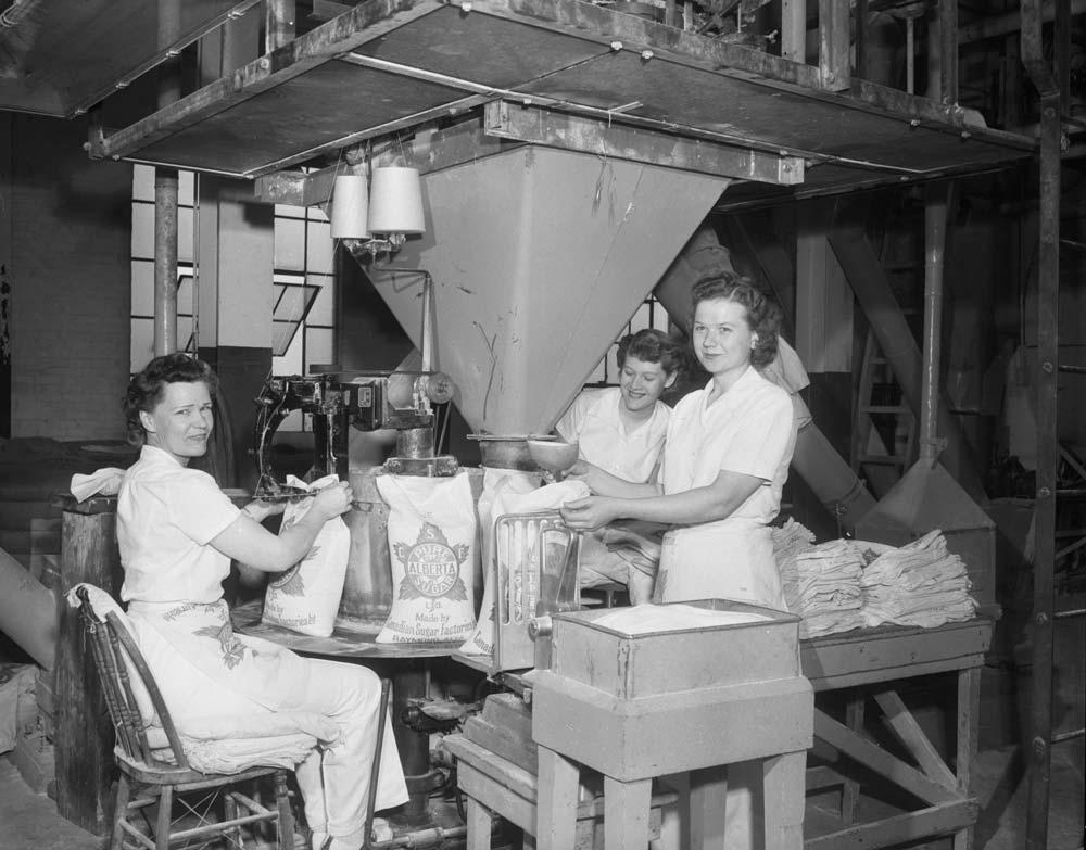 Three women filling bags of sugar in a sugar plant.
