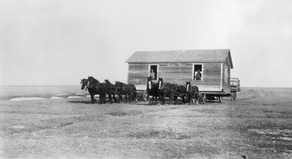 Two teams of horses pull a house lifted onto wagons.