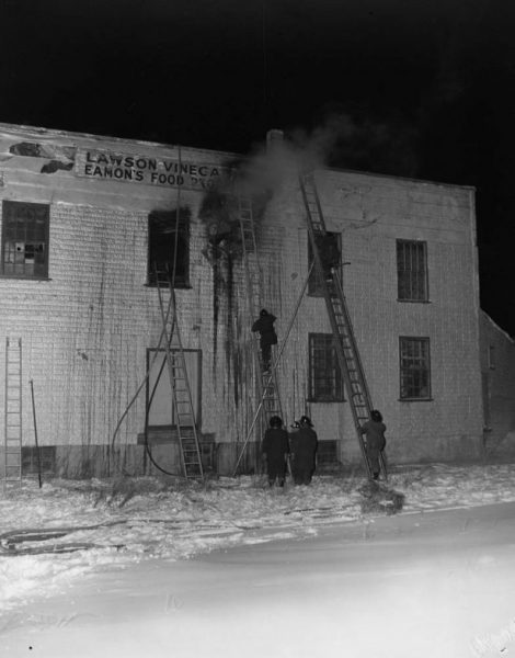 Firefighters scale ladders as they try to put out a fire in a vinegar factory.