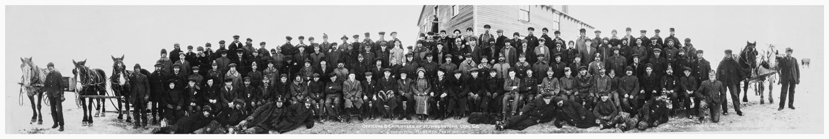 A group of coal miners and horses posing outside for a group photograph as seen in one of the panoramic photos of the Glenbow Archives.