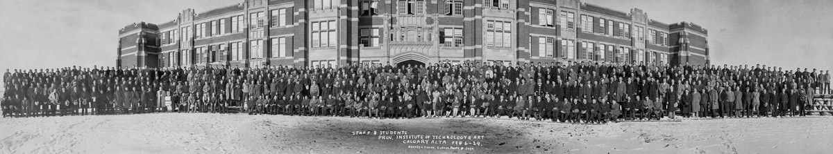 Staff and students of the Provincial Institute of Technology and Art posing outside in front of the school as seen in one of the panoramic photos of the Glenbow Archives.