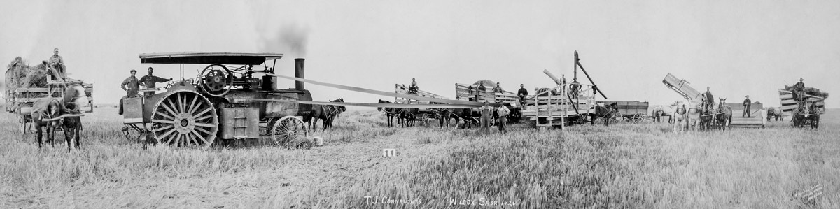 An early threshing tractor at work in a field with horse drawn wagons as seen in one of the panoramic photos of the Glenbow Archives.