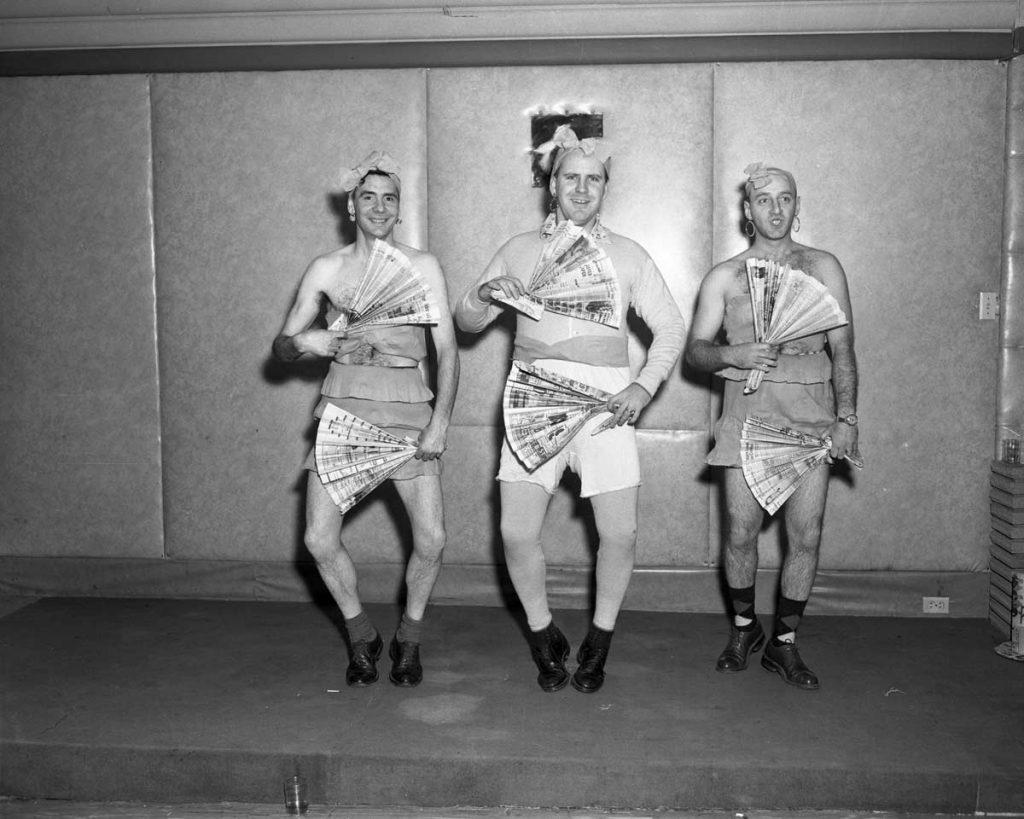 Three men performing a weird, wacky and wild fan dance