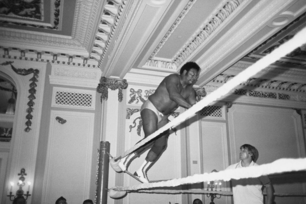 A wrestler leaps from the ropes