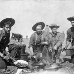 Four Canadian soldiers cook over an open fire in South Africain this photograph used to illustrate military history at the Glenbow.