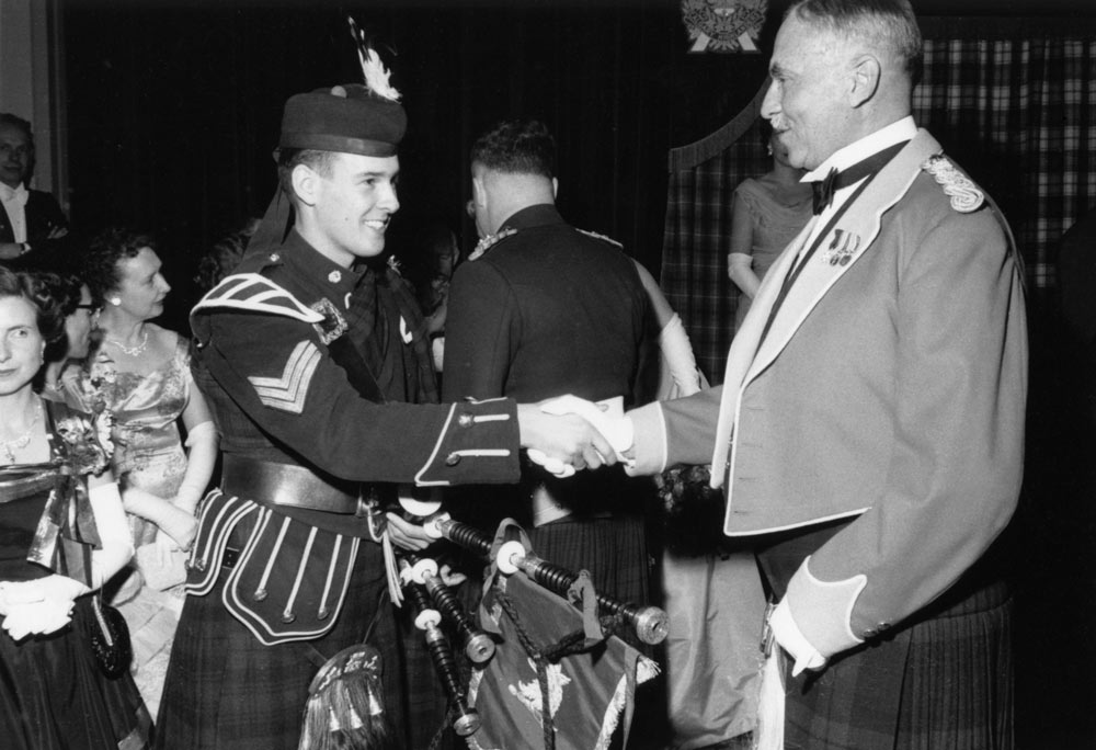 A young soldier shakes hands with Eric L. Harvie, honorary colonel of the Calgary Highlanders in this image used to illustrated Military History at the Glenbow.