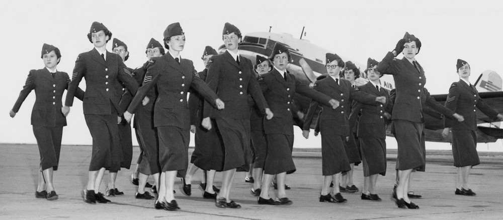 A group of young woman participating in the Royal Canadian Air Cadets march past a plane in this photograph used to illustrate military history at the Glenbow.